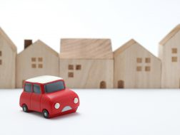 Miniature car and houses on white back ground.